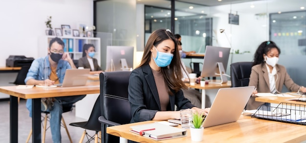 Panoramische groep van bedrijfsmedewerkers draagt een beschermend gezichtsmasker in een nieuw normaal kantoor en oefen op sociale afstand met handdesinfectiemiddel alcoholgel op tafel om verspreiding van coronavirus covid-19 te voorkomen