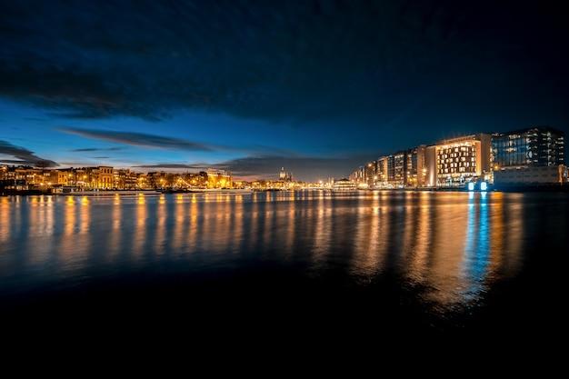 Panoramische opname van de skyline van een nacht met lichtreflecties op het water