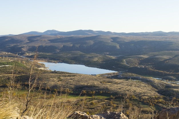 Panoramische opname van een meer tussen glooiende heuvels onder een bewolkte hemel