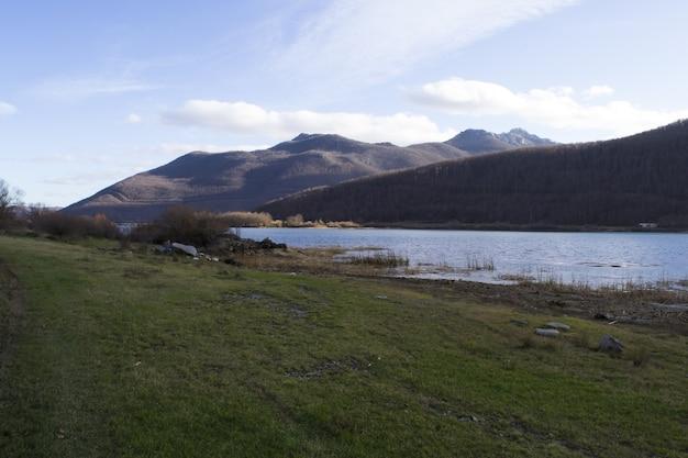 Panoramische opname van een met gras begroeide kustlijn met heuvels