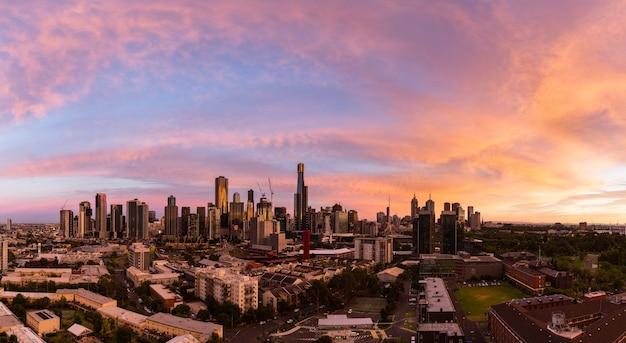 Panoramische opname van een stadsgezicht onder de prachtige oranje lucht tijdens zonsondergang