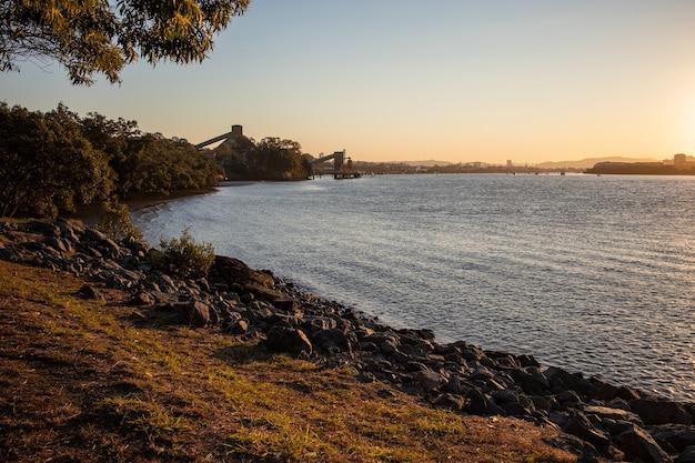 Panoramische opname van een steenachtige kustlijn met de zon aan de horizon