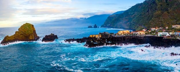 Panoramische opname van golven in de zee die tegen steenformaties beuken