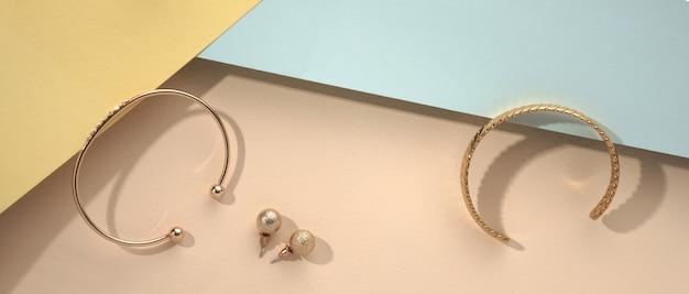 Panoramische opname van gouden accessoires armbanden en oorbellen op kleurrijke achtergrond
