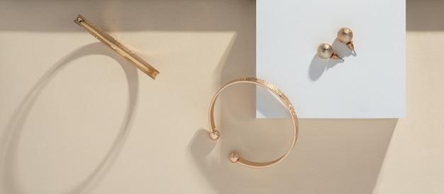 Panoramische opname van gouden armbanden en oorbellen op witte doos op beige achtergrond