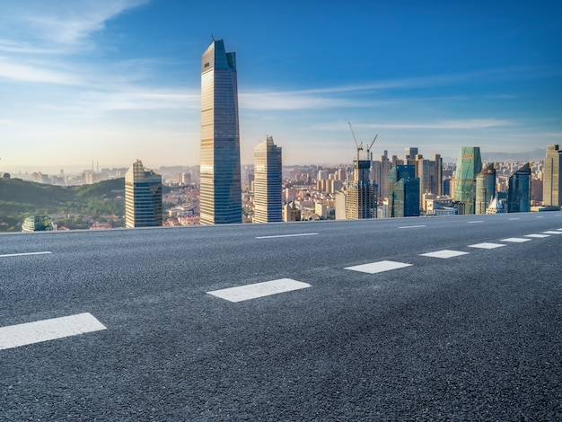 Panoramische skyline en lege asfaltweg met moderne gebouwen