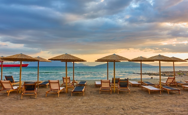 Panorana van leeg strand met ligstoelen en stroparasols aan zee en kleurrijke wolken bij zonsondergang, aegina-eiland, griekenland - grieks landschap - zeegezicht