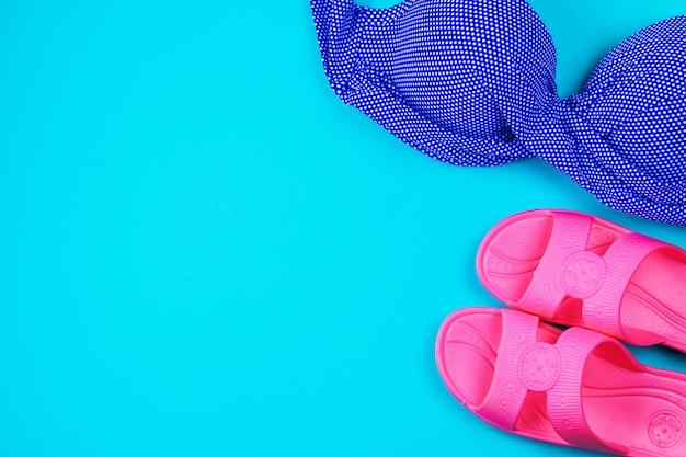 Pantoffels, zwempak, handdoek op een blauwe pastelkleurachtergrond