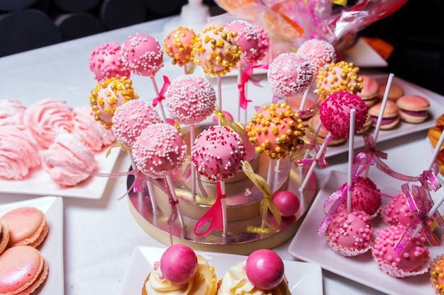 Pap-cakes op stokjes op tafel met snoep