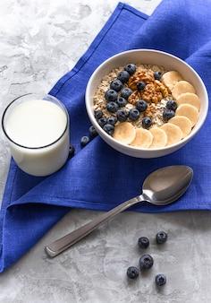 Pap met bananen, bosbessen en walnoot en glas melk voor een gezond ontbijt of lunch.
