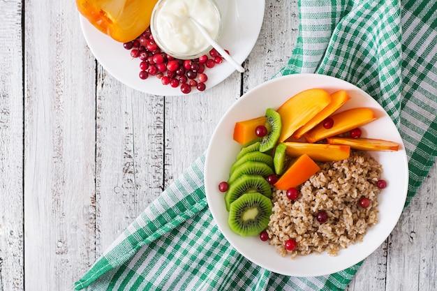 Pap met vers fruit en veenbessen. gezond ontbijt. goede voeding. dieet menu. bovenaanzicht