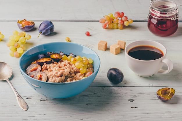 Pap met verse pruimen groene druiven en kopje koffie