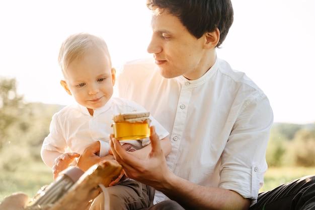 Papa aan het picknicken met zijn zoon buiten de stad zit op een groen gazon met een pot honing in zijn handen