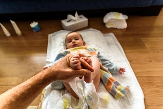 Papa die de voeten van een baby houdt terwijl het veranderen van zijn luier.