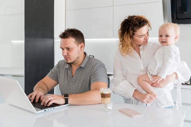 Papa die op laptop werkt