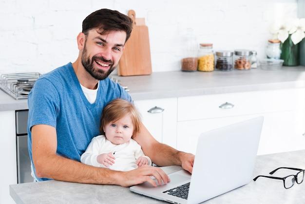 Papa die terwijl het werken aan laptop met baby glimlacht