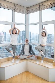 Papa en kinderen doen thuis yoga