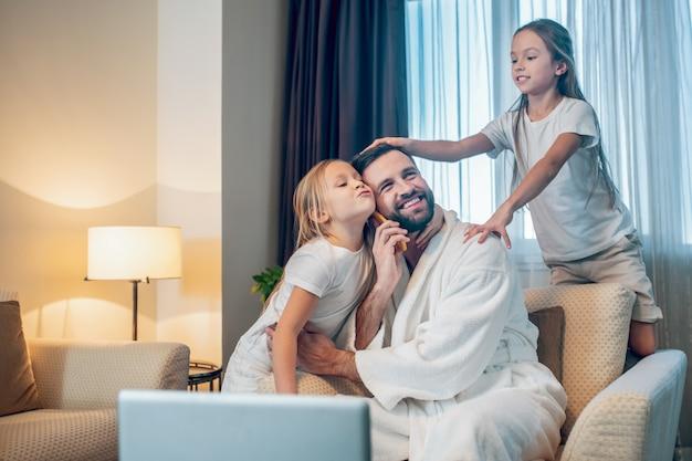 Papa en kinderen. jonge vader die vanuit huis werkt en tijd doorbrengt met zijn dochters