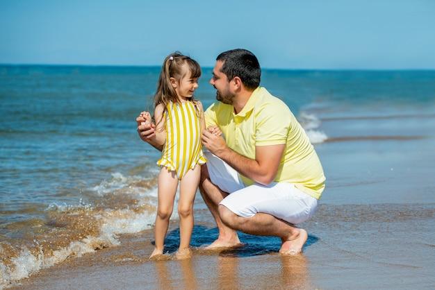 Papa en kleine meid spelen, rennen op het strand en ravotten aan de zeekust. familievakantie op zee met een kind.