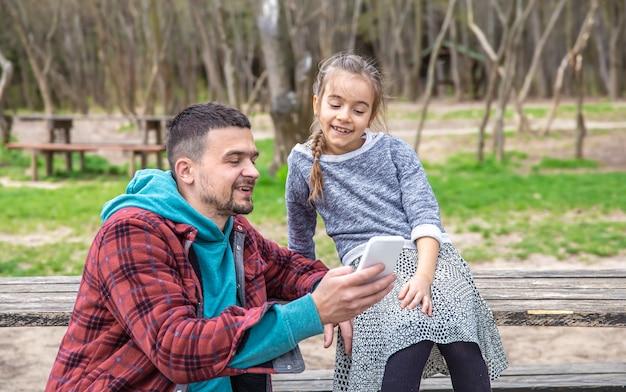 Papa en zijn dochtertje kijken naar de telefoon terwijl ze in het bos wandelen.