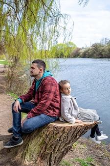 Papa en zijn dochtertje zitten in het vroege voorjaar in het bos bij de rivier en genieten van de natuur.