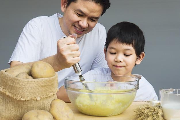 Papa en zoon die fijngestampte aardappels gelukkig maken