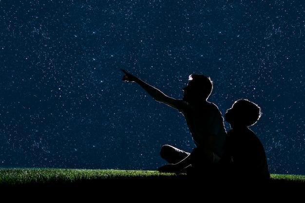 Papa en zoon zitten 's nachts op het gras en kijken naar de nachtelijke hemel
