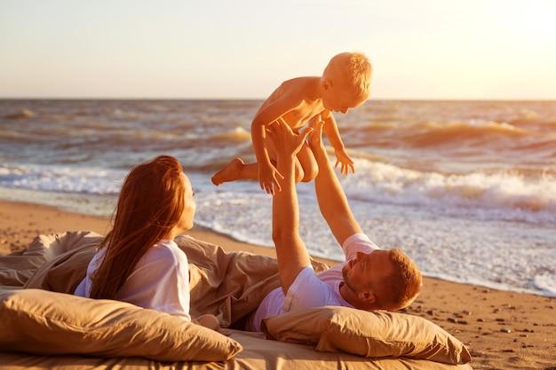 Papa gooit zijn zoon omhoog. lig op een bed bij de zee bij zonsondergang