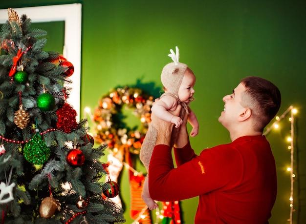 Papa houdt dochtertje in een hert pak poseren voor een kerstboom