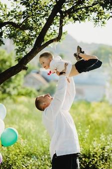 Papa houdt zoontje in geborduurd shirt in zijn armen staande onder groene boom