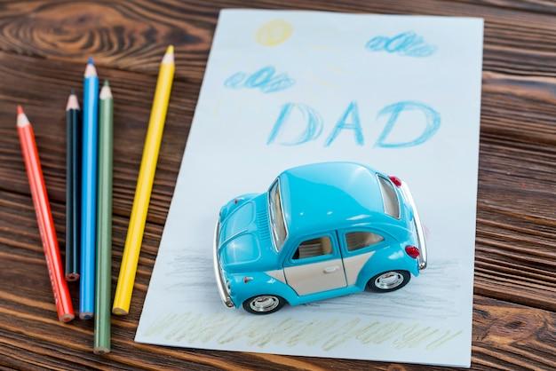 Papa inscriptie met speelgoedauto en potloden