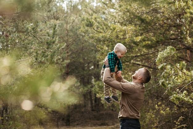 Papa is aan het dollen met zijn zoon. papa gooit zijn zoon in de lucht