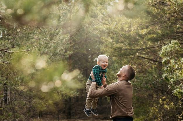 Papa is aan het dollen met zijn zoon. vader gooit zijn zoon in de lucht. vader speelt met zijn zoon. blij kind. vaderdag.