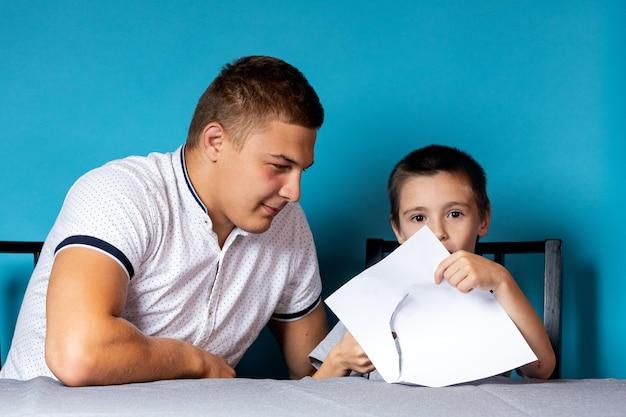 Papa leert het kind thuis, thuisonderwijs. vader helpt zijn zoon met zijn huiswerk, papier knippen