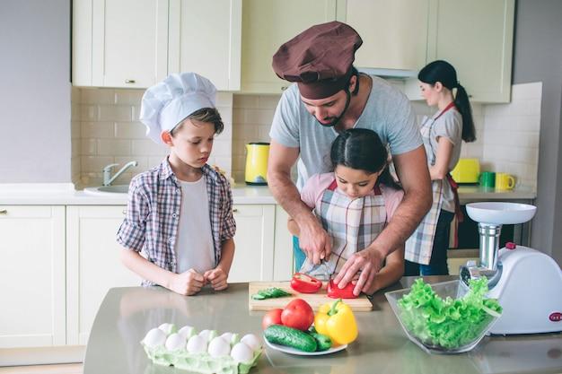 Papa leert meid heet om tomaten te snijden. hij helpt haar. boy kijkt ernaar. hij is geconcentreerd. vrouw staat achter hen en kookt.