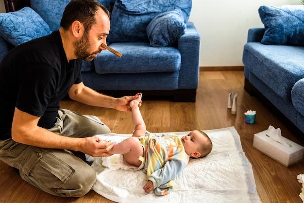 Papa maakt de vuile reet van zijn baby schoon en verandert de stinkende luier met een neusklem, vaderschap en humor.