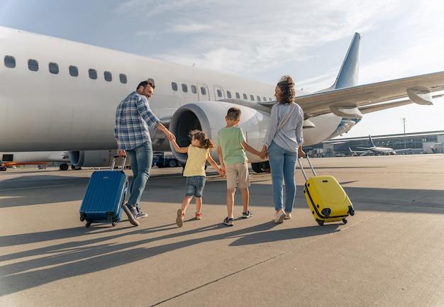 Papa mama en kinderen samen op het vliegveld bij het vliegtuig