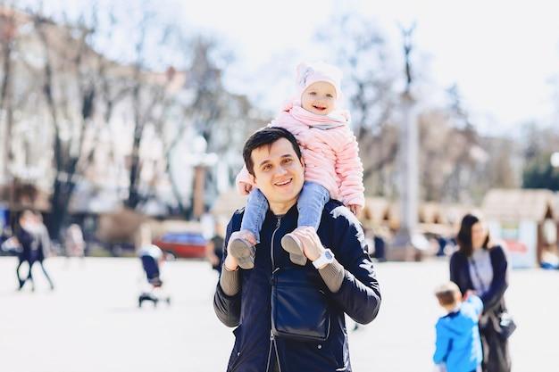 Papa met baby op schouders lopen op straat