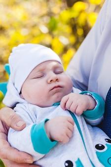 Papa met een baby, een kleine jongen loopt in de herfst in het park of bos. gele bladeren, de schoonheid van de natuur. communicatie tussen een kind en een ouder.