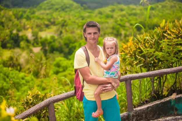 Papa met zijn dochter die in tropisch park bij de chocoladeheuvels loopt