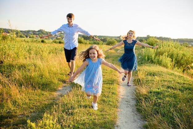 Papa, moeder en dochter hebben samen plezier in de natuur.