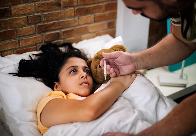 Papa neemt de temperatuur van zieke dochter