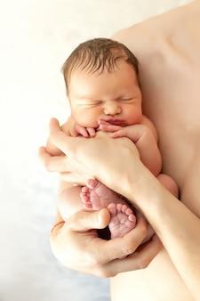Papa's handen houden slapende pasgeboren babyjongen