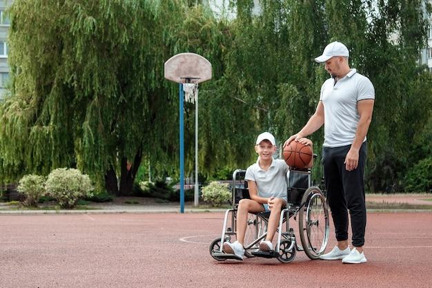 Papa speelt met zijn gehandicapte zoon op het sportveld. concept rolstoel, gehandicapte, vervullend leven, vader en zoon, activiteit, opgewektheid, basketbal.