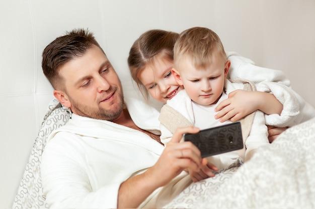 Papa toont kinderen interessante foto's in de telefoon