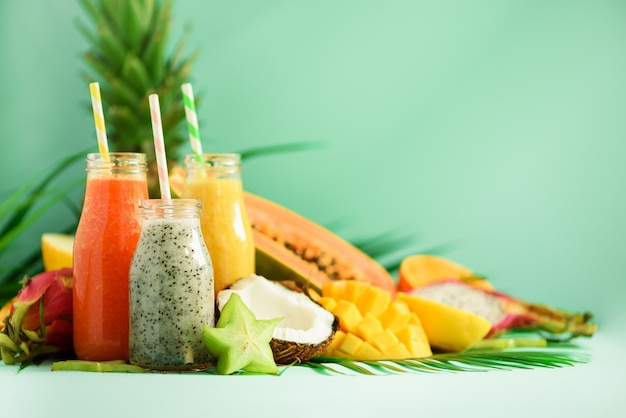 Papaja, dragon fruit, ananas, mango smoothie in potten op turkooizen achtergrond. detox, veganistisch dieetvoeding, gezond eetconcept.