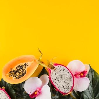 Papaja; dragon fruit; bladeren en orchideebloem tegen gele achtergrond