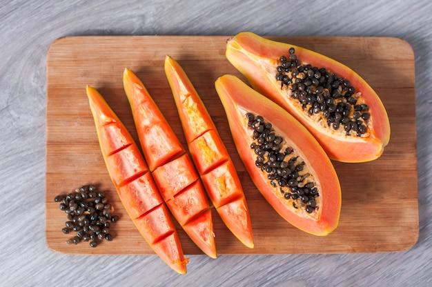 Papajafruit dat in plakken op houten achtergrond wordt gesneden