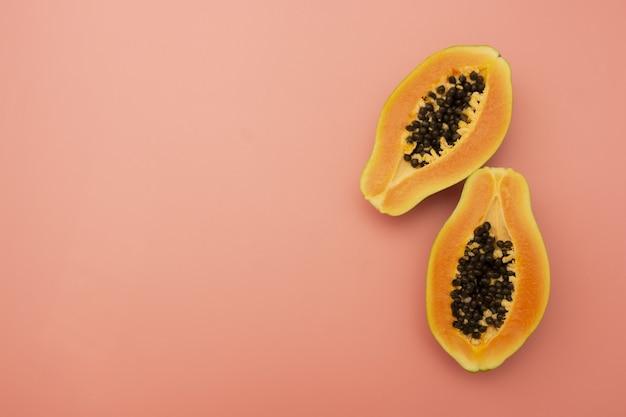 Papajafruit dat over roze achtergrond wordt geïsoleerd. kopieer ruimte.