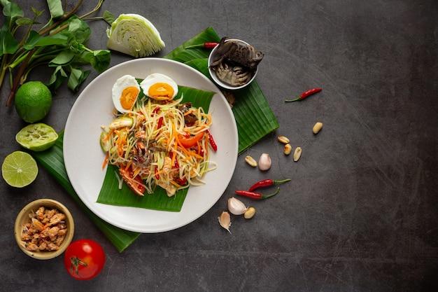 Papajasalade geserveerd met rijstnoedels en groentesalade versierd met thaise voedselingrediënten.